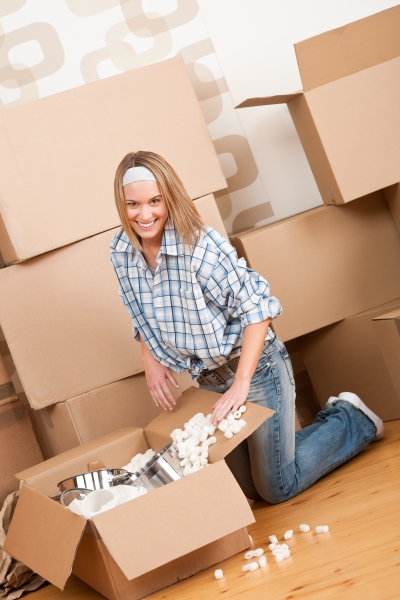 1606573-moving-house-happy-woman-unpacking-box